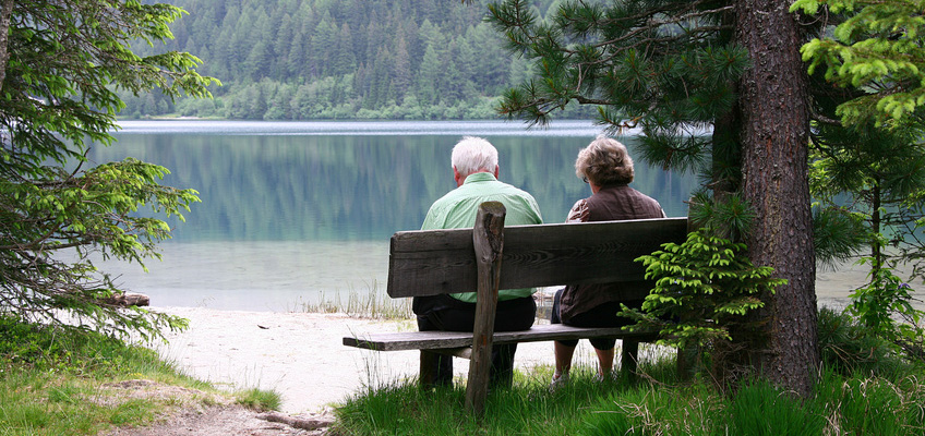 a couple sitting together on a bench with forrest surrounding a lake